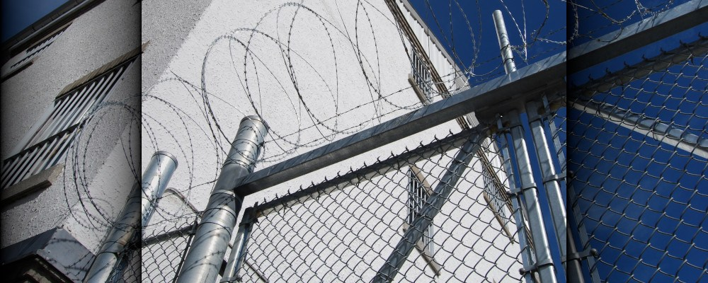 Poor communication in prison inspired this blog - Picture of prison building and barbed wire gate.