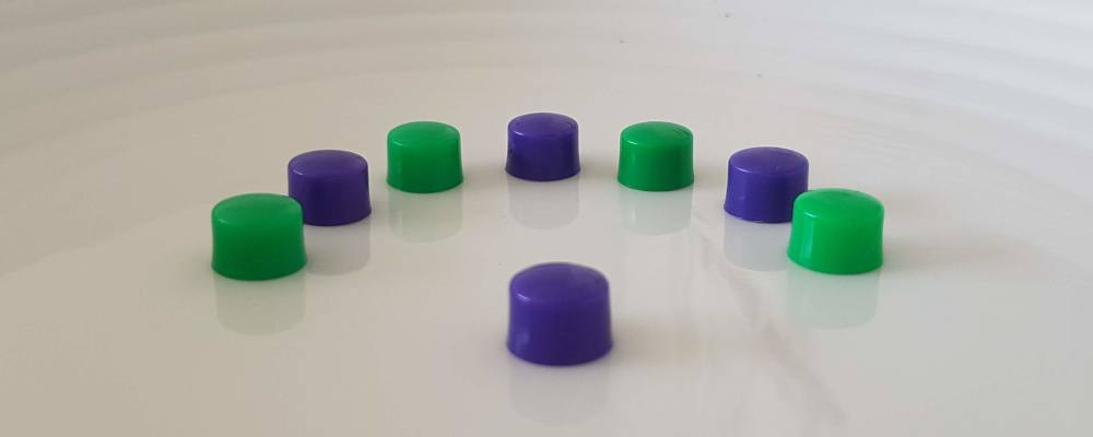 Feature image for the Article '7 Unique Active Listening games, exercise and activities for Adults. Seven purple and green board counters in a semi-circle facing a single purple counter.